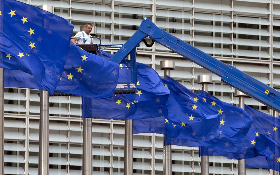 FILE- In this June 23, 2016 file photo, a worker on a lift adjusts the EU flags in front of EU headquarters in Brussels. The European Union's enlargement policy is at an impasse as its leaders gather for a summit focused on how to deal with Western Balkans neighbors that have been trying to enter the club for two decades. Meanwhile, the region is increasingly getting support from China and Russia instead.