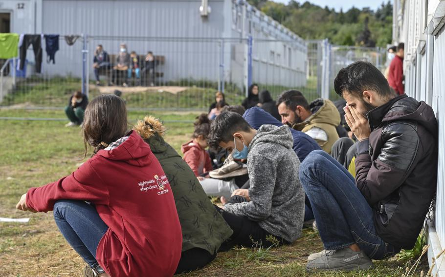 Migrants sit in front of containers at the Central Initial Reception Facility for Asylum Seekers, ZABH, in the federal German state of Brandenburg in Eisenhuettenstadt, Germany, Wednesday, Oct. 6, 2021. German federal police said more than 4,300 people crossed the border from Poland 'illegally' this year. Most people are being put up at asylum centers in the eastern state of Brandenburg.