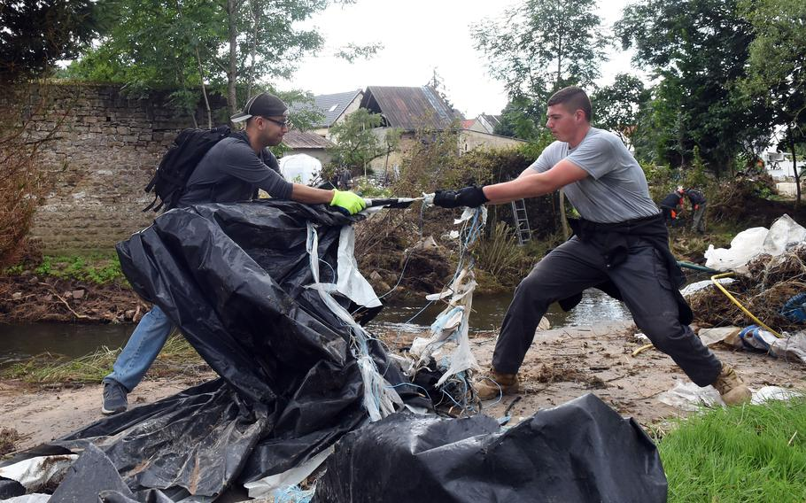 Senior Airman Calixto Rodriguez, left, and Airman Kyle Koury try to break apart a piece of debris while cleaning up the banks of the Nims River in Rittersdorf, Germany, on July 31, 2021. More than two dozen airmen from Spangdahlem Air Base volunteered to help clean in the aftermath of last months severe flooding in western Germany.