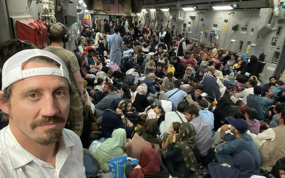 Tim Kennedy, a U.S. Army Green Beret and a mixed martial artist, takes a photo of himself and evacuees inside a U.S. military cargo plane, in an undated photo taken during the evacuation of at-risk people from Afghanistan in the last two weeks of August 2021. Kennedy traveled to Kabul, Afghanistan as a private citizen affiliated with an ad hoc volunteer group that formed to help evacuations.