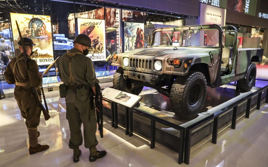 Two active-duty soldiers dressed in period uniforms check out a Jeep at the National Museum of the United States Army on its reopening day, June 14, 2021.