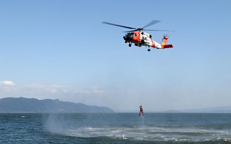 An MH-60 Jayhawk helicopter crew from Coast Guard Sector Columbia River hoists an aviation survival technician from the Columbia River during rescue training in Warrenton, Oregon, Tuesday, April 20, 2021.