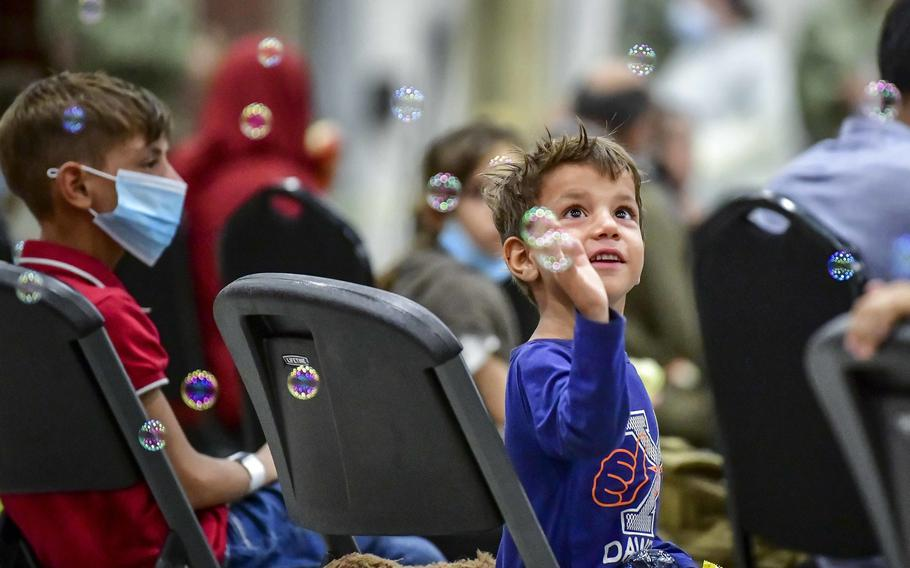 An Afghan child evacuee plays with bubbles after arriving at Naval Air Station Sigonella, Sicily, Aug. 22, 2021.