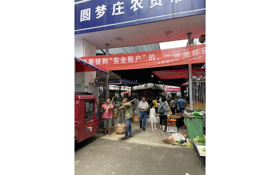 Shoppers at the entrance to Yuanmengzhuang market in China's Enshi city. A chicken vendor recalled live wildlife being sold there as recently as late 2019. In March 2020, local authorities banned meat and vegetable stores and other mobile stalls from operating outside the designated market area.