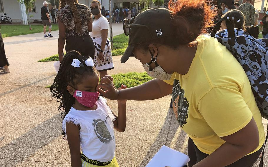 Keturah Ernest and her 6-year-old daughter, Kaleigh B, get ready to take back-to-school photos outside Naples Elementary School at the Gricignano di Aversa site on Naval Support Activity Naples, Monday, Aug. 23, 2021.