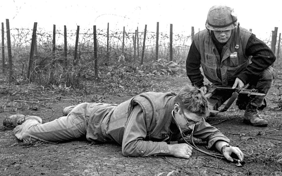 Khe Sanh, South Vietnam, March 1968: Hospital Corpsman Theodore Rutkowski of Pittsburgh lies on the ground just outside of Khe Sanh's outer defenses and uses a stethoscope to listen for signs of Viet Cong tunneling beneath the beleaguered base.