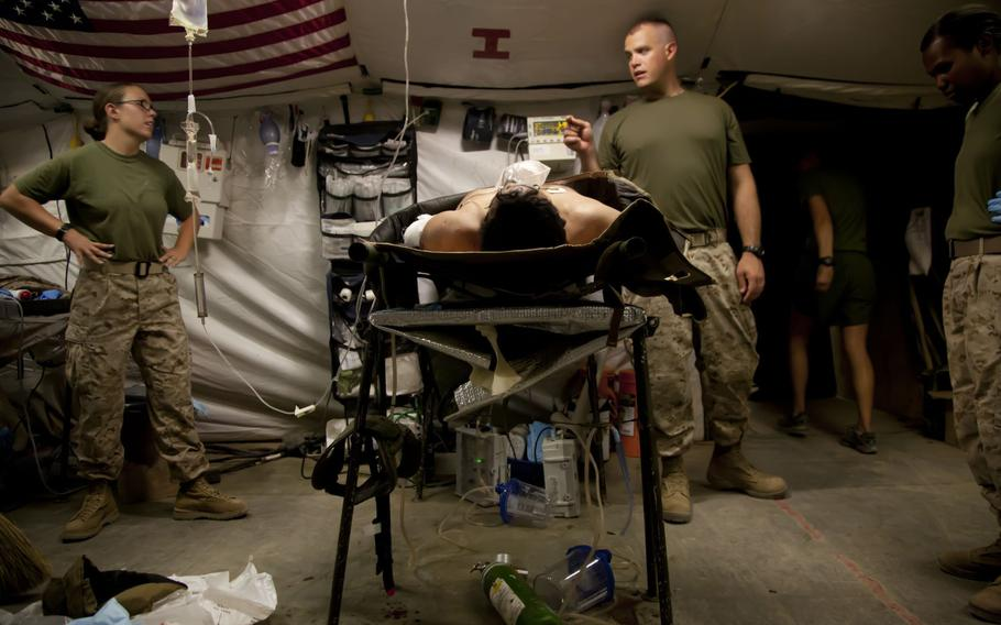Medical personnel at Forward Operating Base Edinburgh in Helmand Province, shown here in June 2012, discuss the case of a patient.
