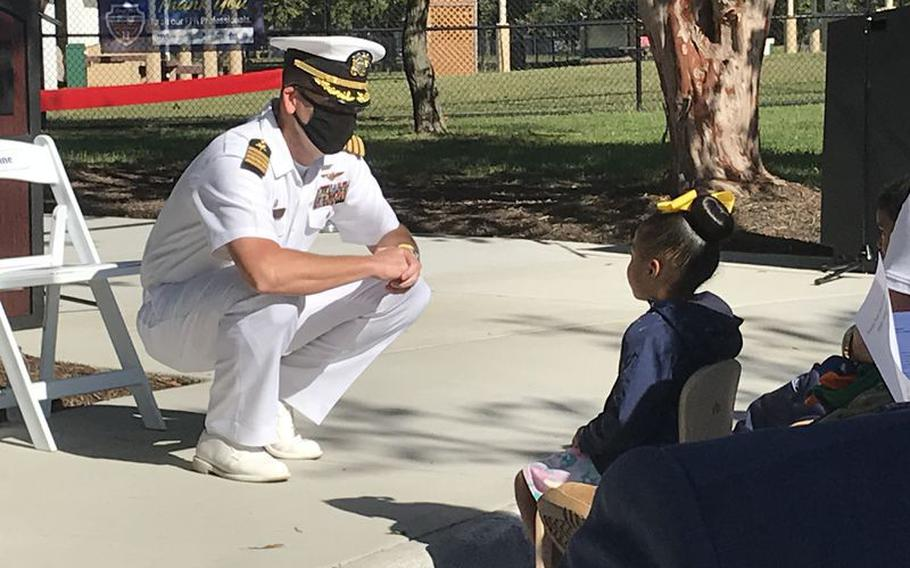 Capt. Jonathan Kine, commanding officer of Naval Support Activity Hampton Roads, chats with some of the children at the October reopening of Sewells Point Child Development center.