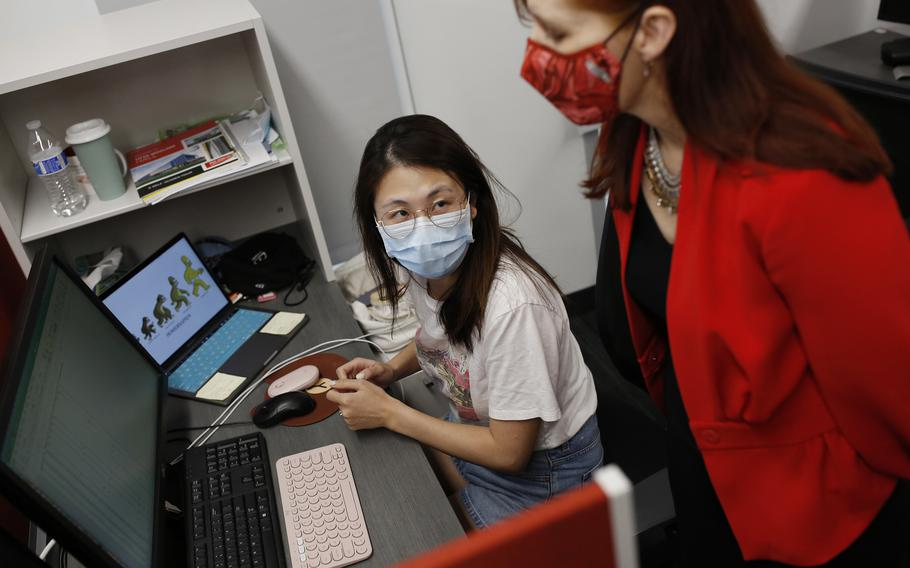 Julie Swann, right, head of the Fitts Department of Industrial and Systems Engineering at North Carolina State University, looks over the work of doctoral student Yiwei Zhang.