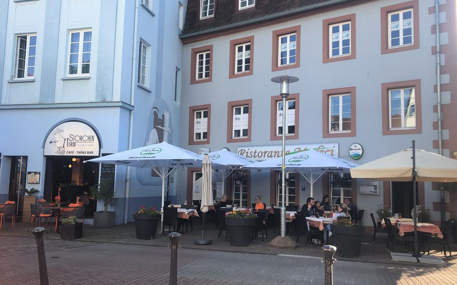 People eat outside near the market square in Kaiserslautern, Germany. Under new coronavirus rules in the state of Rheinland-Pfalz, shops and restaurants will be allowed to stay open when COVID-19 numbers rise above certain levels.
