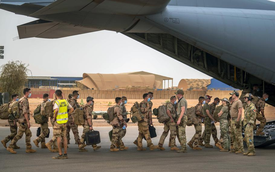 French Barkhane force soldiers board a US Air Force C130 transport plane as they leave their base in Gao, Mali Wednesday June 9, 2021. France has suspended joint military operations with Malian forces until the junta led by Col. Assimi Goita, who retook control of Mali's transitional government May 24, complies with international demands to restore civilian rule.