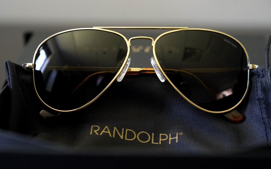 A pair of Randolph Engineering Concorde teardrop sunglasses, in 23-karat gold finish with polarized American gray lenses, rest on a table at the company where they are made, in Randolph, Mass., Thursday, June 17, 2021.