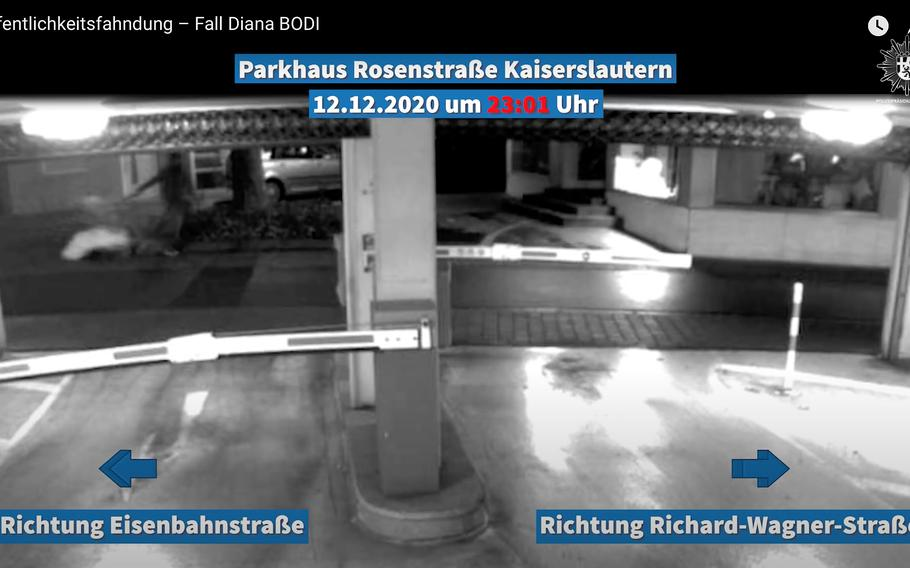A screenshot from a video released by the German police July 22, 2021, shows a man pulling a shopping cart with a large object wrapped in white past a downtown Kaiserslautern parking garage last December. The man is a suspect in the death of Hungarian home care provider Diana Bodi, whose body was found in a nearby alley days after the video was shot.