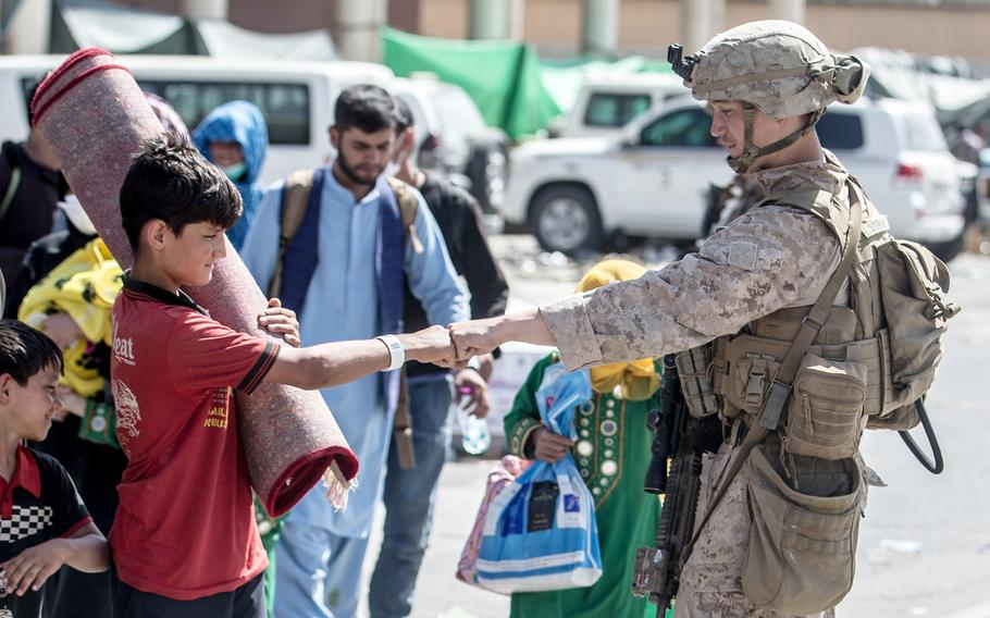 A U.S. Marine greets a child being evacuated out of Hamid Karzai International Airport in Kabul, Afghanistan, Aug. 24, 2021.