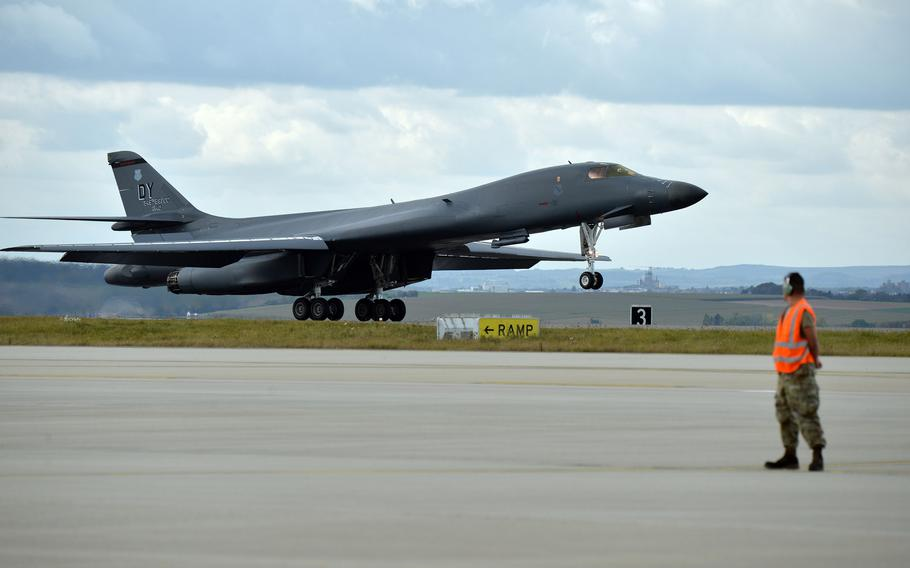 An airman watches as a B-1B Lancer lands at Spangdahlem Air Base, Germany, Oct. 11, 2021. A pair of Bones, from the 9th Expeditionary Bomb Squadron, Dyess Air Force Base, Texas, refueled at the base following a mission over Lithuania.
