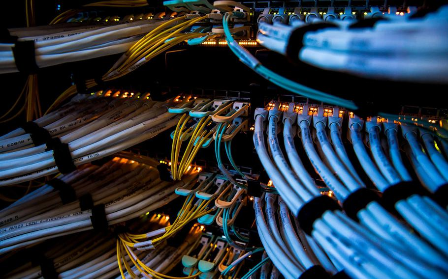 Fiber optic cables, center, and copper Ethernet cables feed into switches inside a communications room at an office in London.