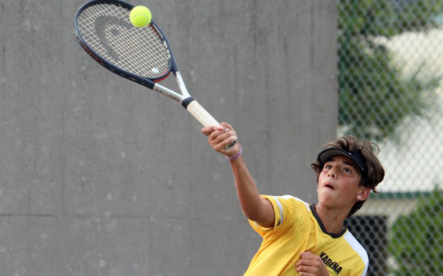 Kadena's Marco Leone hits an overhead smash during Wednesday's Okinawa tennis mixed doubles matches. Leone and partner Celeste Pallares beat Kubasaki's Aidan Shaver and Victoria Lawrence 8-4.