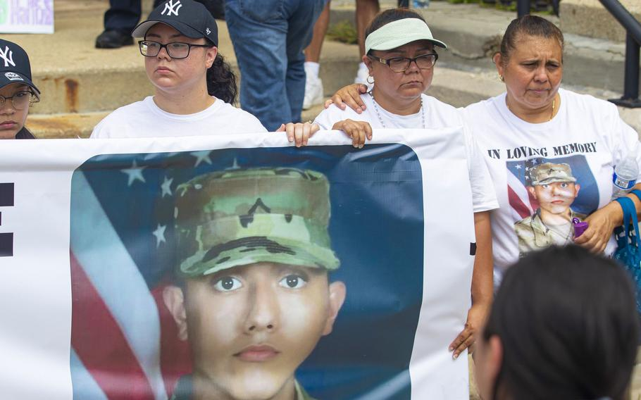 Jennifer Ramirez, left, and Lourdes Lara, the sister and mother of 19-year old National Guard member Chrys Carvajal, killed over the July Fourth weekend, hold a banner with Carvajal's photo on it during a rally for peace at Riis Park in the Belmont-Cragin neighborhood of Chicago on Saturday, July 24, 2021.