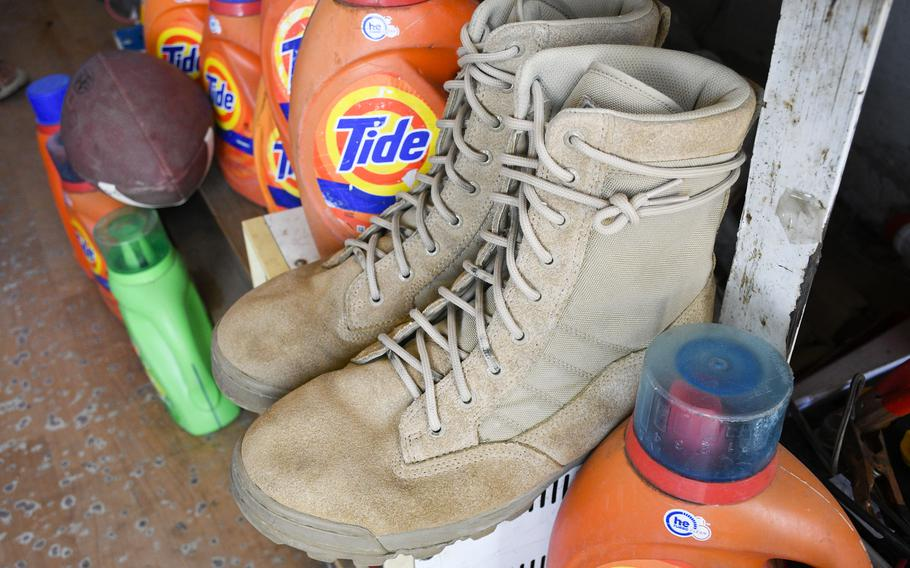 Boots like those issued by the U.S. military and a football are displayed prominently at a shop outside Bagram Airfield, Afghanistan, June 5, 2021. None of the shopkeepers said they knew what the American football was for.
