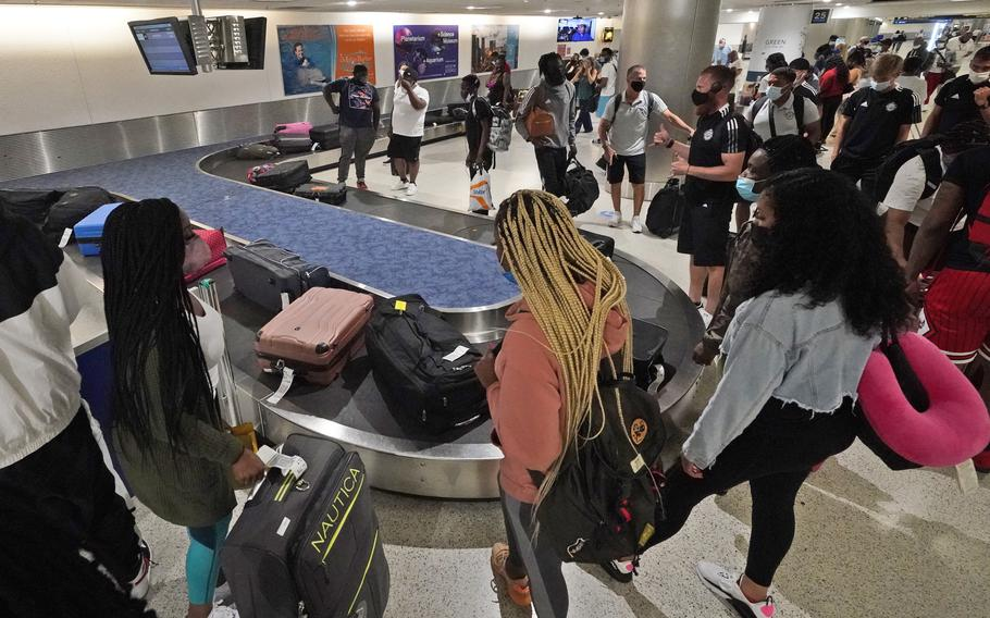 Travelers wait for their luggage at a baggage carousel at Miami International Airport on May 28, 2021.