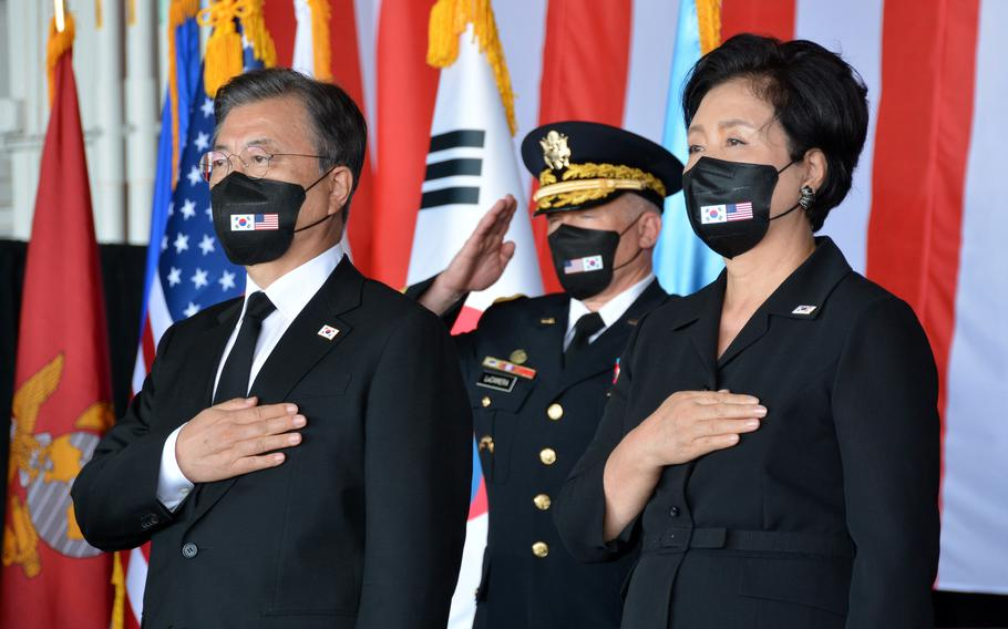 South Korea President Moon Jae-in and his wife, Kim Jung-sook, stand during a remains repatriation ceremony at Joint Base Pearl Harbor-Hickam, Hawaii, Wednesday, Sept. 22, 2021. The commander of U.S. Forces Korea and United Nations Command, Gen. Paul LaCamera, salutes behind them.