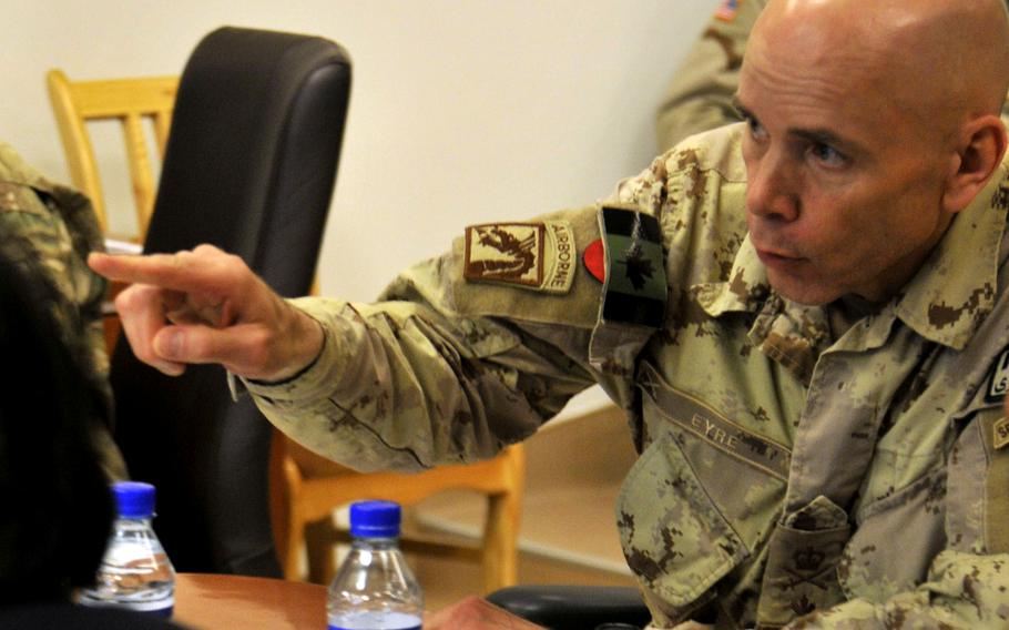 Then-Brig. Gen. Wayne Eyre, the Canadian army commander of NATO Training Mission-Afghanistan, talks with Afghan army and police leaders in 2014. Now a lieutenant general and the acting head of Canada's armed forces, Eyre wrote a public letter acknowledging questions about the legacy of their time in Afghanistan, after the Taliban took control of Panjwai district in southern Kandahar province, where many Canadians fought and died.