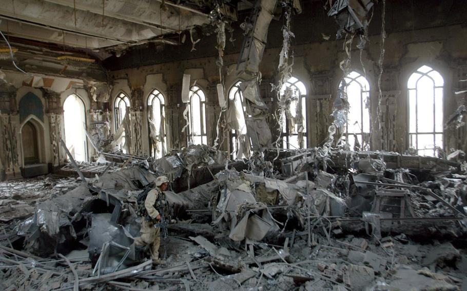 In this April 7, 2003, file photo, U.S. Army soldiers from A Company, 3rd Battalion, 7th Infantry Regiment, search one of Saddam Hussein's palaces damaged after a bombing in Baghdad.  The U.S. launched its invasion of Iraq on March 20, 2003, unleashing a war that led to an insurgency, sectarian violence and tens of thousands of deaths.