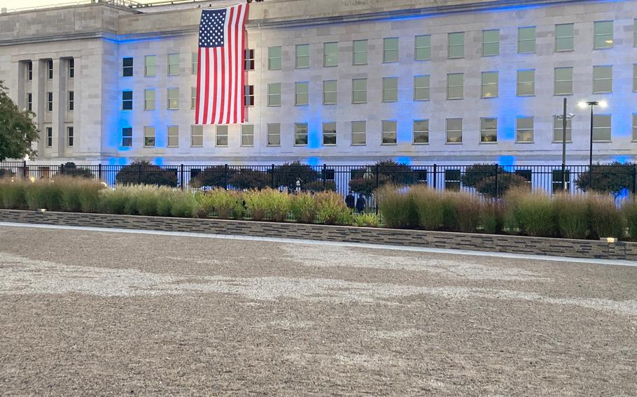The Pentagon's first event of the day was the flag unfurling, which took place at 6:47 a.m. The side of the building was lit up blue. There were a couple dozen people in attendance. Bagpipe players performed before the flag was unfurled.