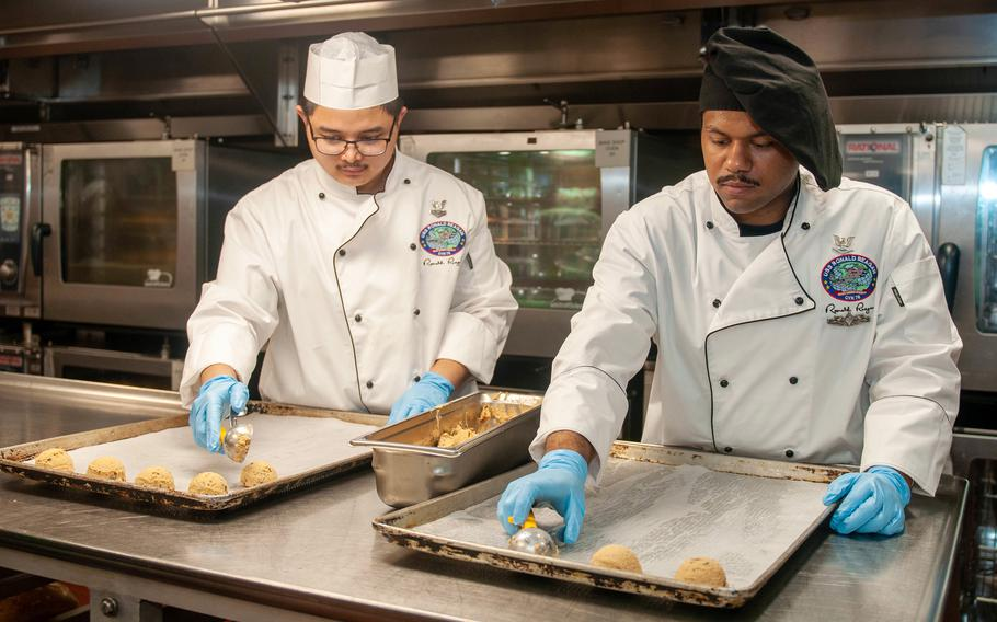 Petty Officer 2nd Class Carllouis Obieta, left, and Petty Officer 3rd Class Justin Padilla prepare cookies aboard the USS Ronald Reagan in the Arabian Sea, July 5, 2021, in honor of Nancy Reagan's 100th birthday.