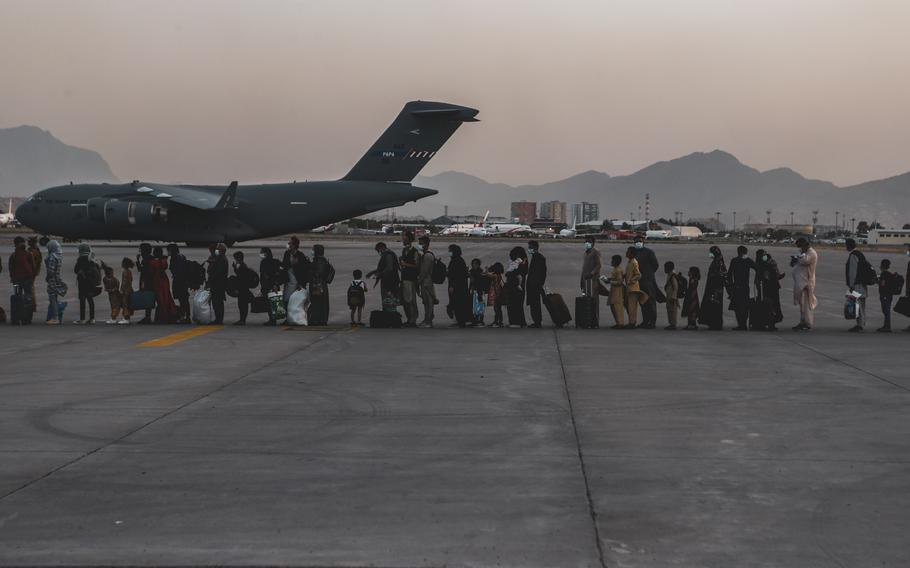 """Evacuees wait to board a Boeing C-17 Globemaster III during an evacuation at Hamid Karzai International Airport, Kabul, Afghanistan, Aug. 23, 2021. Qatar expects to have Kabul's airport """"operational very soon"""" and has urged the Taliban to help facilitate the evacuation of Afghans stranded after the end of a massive U.S. airlift staged as its last troops left the country."""