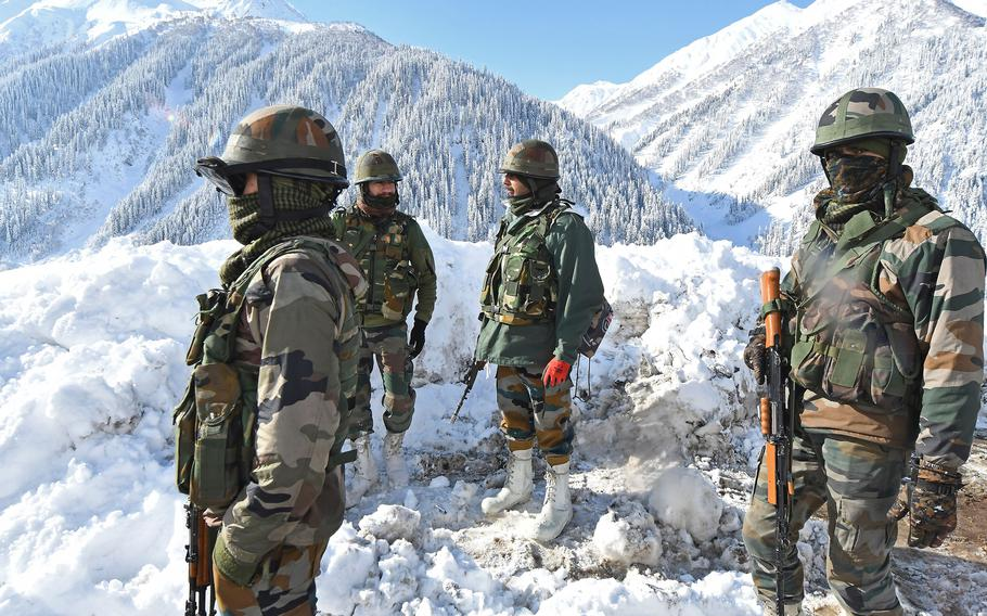 Indian army soldiers stand on a snow-covered road near Zojila mountain pass that connects Srinagar to the union territory of Ladakh, bordering China on Feb. 28, 2021.