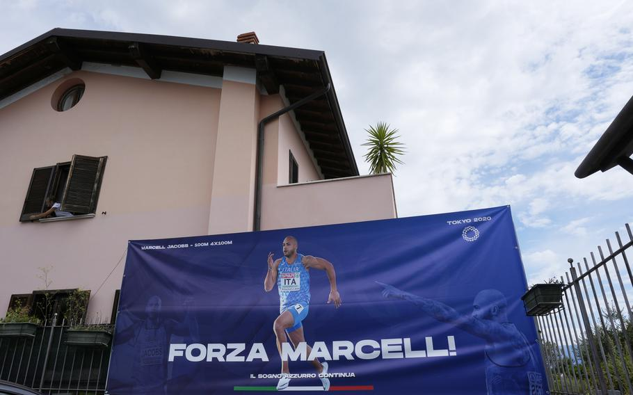 """A poster reading """"Go Marcell"""" for Italy's Lamont Marcell Jacobs, the gold medalist in the 100 meters at the Tokyo Olympics, is seen in front of the hotel Florence, run by his mother Viviana Masini in Manerba del Garda, Italy, Monday, Aug. 2, 2021."""