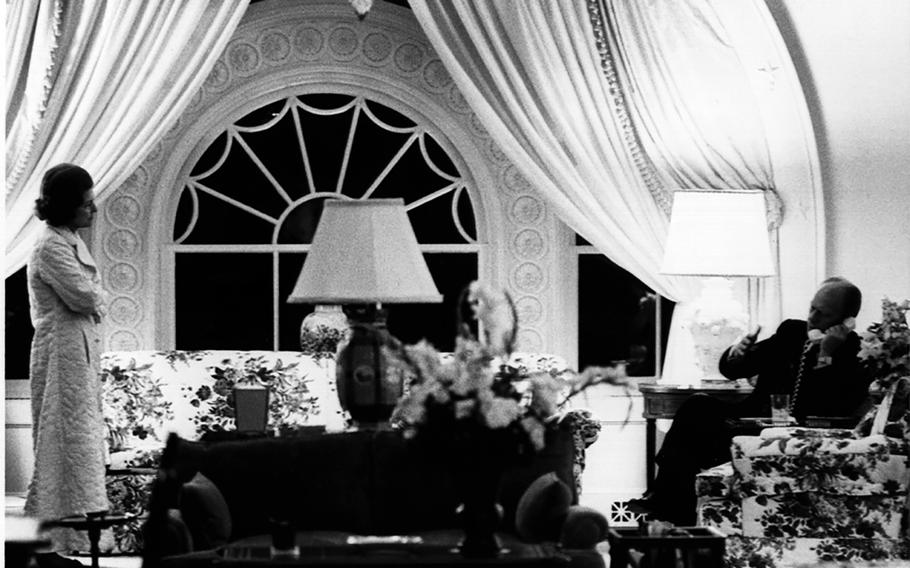 President Gerald Ford makes a late-night phone call involving the evacuation of Saigon as first lady Betty Ford looks on, April 28, 1975.