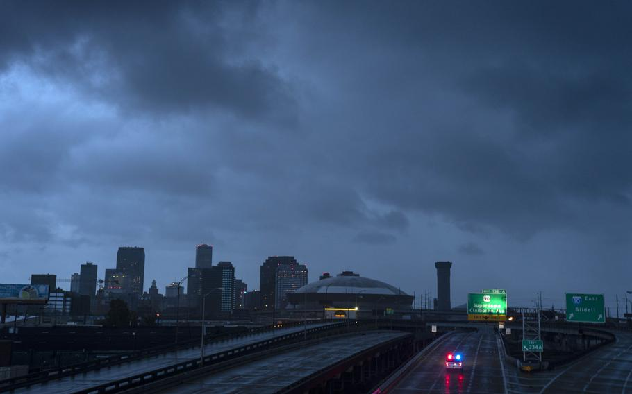 The downtown skyline is largely shrouded in darkness during the dawn as the electricity throughout Orleans Parish has failed after Hurricane Ida pummeled the area.