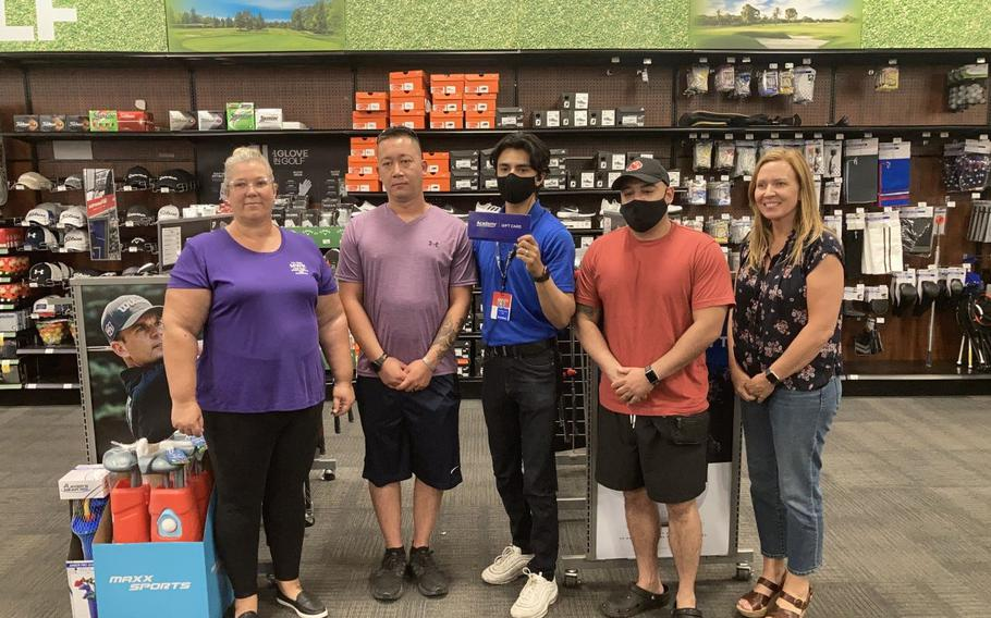 Marlo Brestar, left, and Michele Wiernicki, far right, both from the Fort Bliss Morale, Welfare and Recreation Division, and Academy Sports + Outdoor store employee Jacob Arellano rewarded the two winning military dads, Sgt. 1st Class Kyle Tranchitello and Staff Sgt. Eddie Hernandez, with $1,000 gift cards.