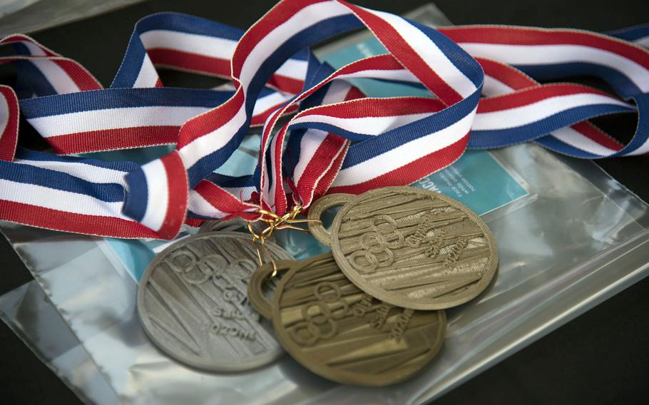 Replica Olympic medals, 3D-printed, are placed inside a time capsule at Yokota Air Base, Japan, Thursday, July 29, 2021.