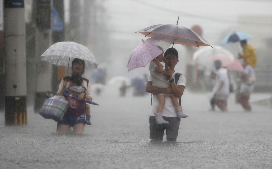 People wade through a road flooded by heavy rain in Kurume, Fukuoka prefecture, western Japan, Saturday, Aug. 14, 2021. Torrential rain continued to trigger floods Saturday in wide areas of southwestern Japan, damaging homes and disrupting transportation.