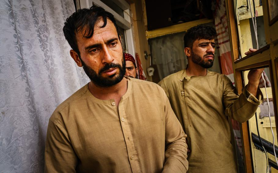 Emal Ahmadi, left, looks off into the distance as relatives around him try to provide support after a U.S. drone strike killed members of his family in Kabul, Afghanistan.