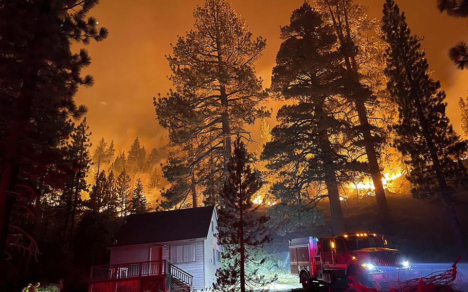 Firefighters protect a home from the Caldor Fire off of S. Upper Truckee Road  in the Christmas Valley area of the Tahoe Basin, Monday evening, Aug. 30, 2021, near South Lake Tahoe, Calif.