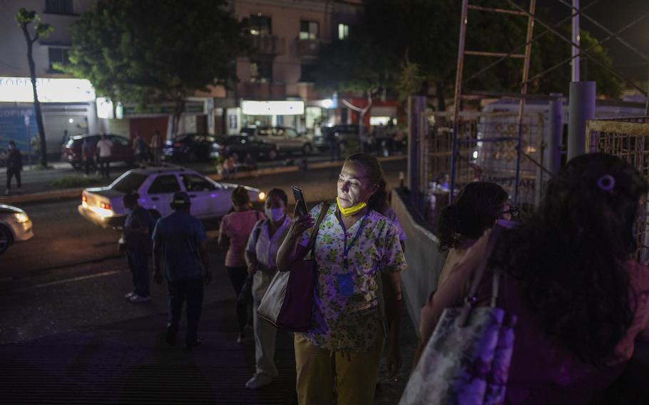 Health workers check their mobile phones as they stand outside Veracruz General Hospital after a strong earthquake, in Veracruz, Mexico, Tuesday, Sept. 7, 2021. The quake struck southern Mexico near the resort of Acapulco, causing buildings to rock and sway in Mexico City nearly 200 miles away.