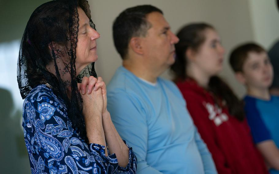 Julie Meyer, of Gaithersburg, Md., prays with her family during a mass at Saint Paul Catholic Church in Damascus, Md., on June 5, 2021.