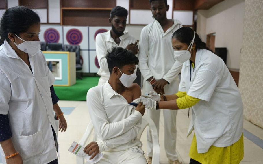 A health worker inoculates a young cricketer with the jab of Covishield vaccine against the COVID-19 coronavirus during a vaccination drive at Rajiv Gandhi International Cricket Stadium in Hyderabad on June 28, 2021.