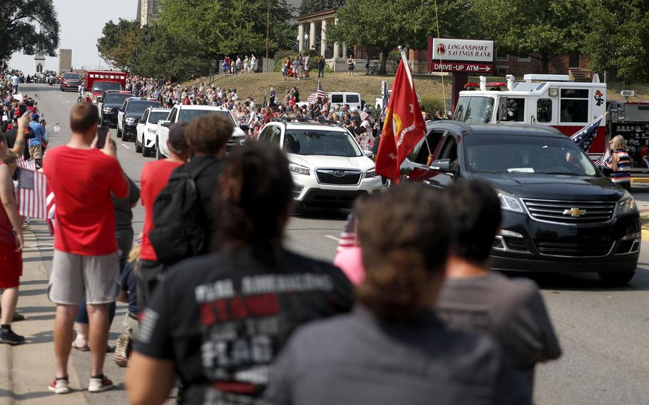 People watch the funeral procession pass by for Marine Corps Cpl. Humberto  Sanchez on Sunday, Sept. 12, 2021, in Logansport, Ind.