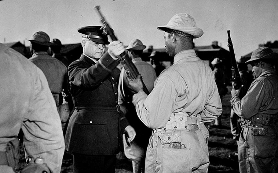 Brig. Gen. Benjamin O. Davis Sr. inspects the rifle of a U.S. African American soldier somewhere in England, probably in 1942. In September 1942, Davis was assigned to the Europe on special duty as an adviser on issues involving Black soldiers. In 1943, a bloody battle between Black and white U.S. soldiers took place at Bamber Bridge, England.