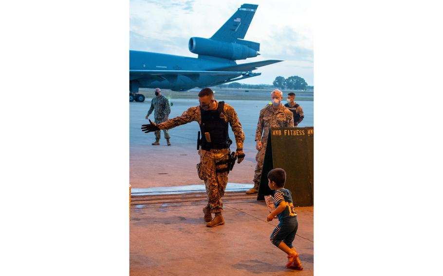 A sailor stationed at Naval Station Rota, Spain, directs a child evacuee from Afghanistan to a check-in station after his arrival at the base aboard a U.S. Air Force KC-10 Extender, Sept. 1, 2021.