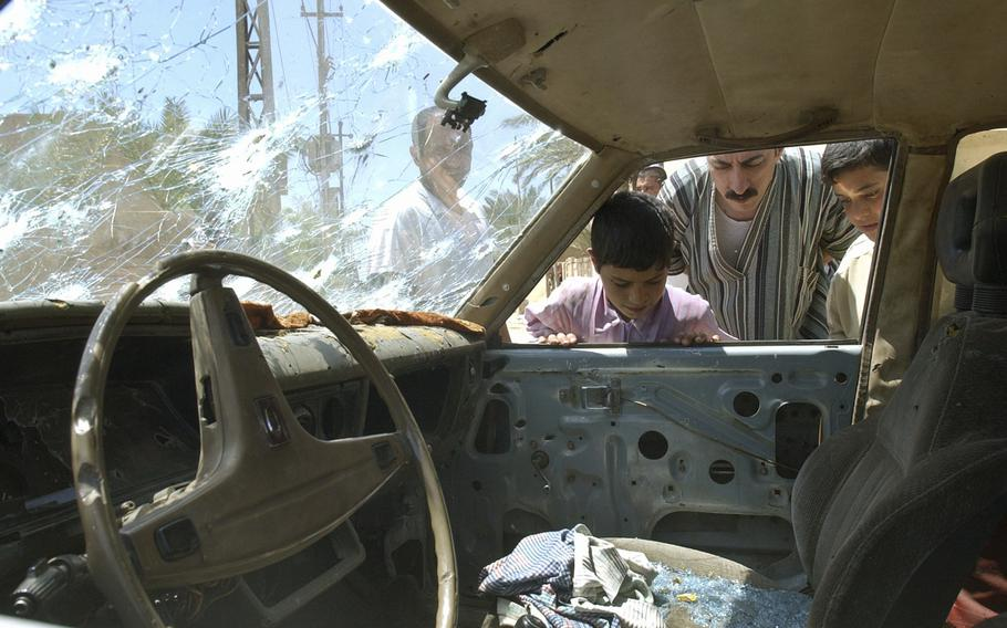 In this April 29, 2003, file photo, residents of Fallujah, Iraq, look into a bullet-riddled car outside a school where U.S. soldiers fired on demonstrators the night before.