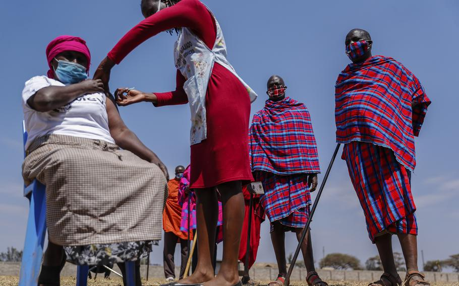 Maasai men line up to receive the AstraZeneca coronavirus vaccine look over as a woman, who is not Maasai. receives a jab at a clinic in Kimana, southern Kenya Saturday, Aug. 28, 2021. Plans for COVID-19 booster shots in some Western countries are highlighting vast disparities in access to vaccines around the world.