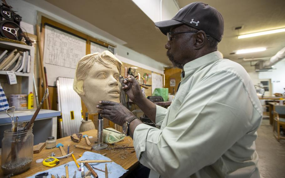In his studio in Lubbock, Texas., Eddie Dixon demonstrates how he adds details to the eyes of a sculpture. He designed a Buffalo Soldier for the U.S. Military Academy.
