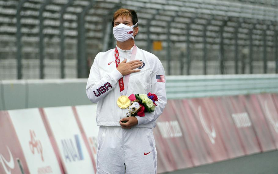 Army veteran Shawn Morelli stands for the U.S. national anthem after winning a gold medal in Paralympic road cycling at Fuji International Speedway outside Tokyo, Tuesday, Aug. 31, 2021.