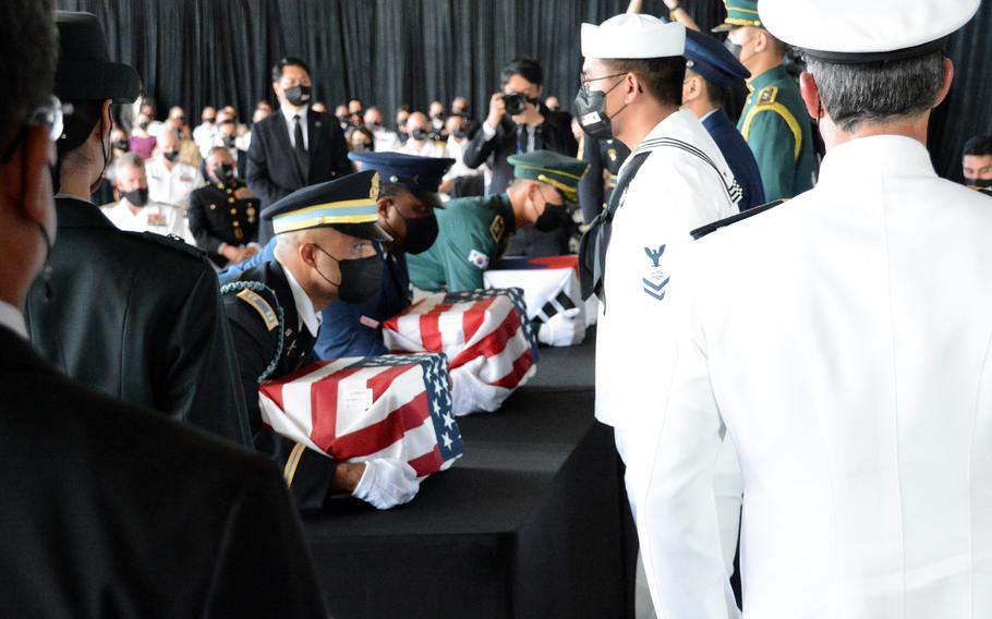 Members of a South Korean-American honor guard lift boxes holding the remains of service members killed in the Korean War during a repatriation ceremony at Joint Base Pearl Harbor-Hickam, Hawaii, Wednesday, Sept. 22, 2021.
